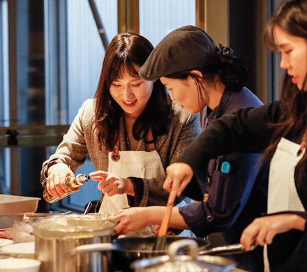 Jieun Choi (far left) cooks at a training session for new entry-level employees at Hyundai Card Cooking Library.